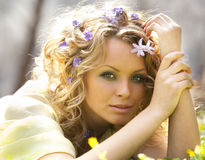 Young girl and  spring flowers in her hair Stock Photos