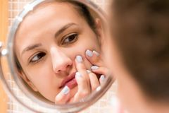 Young girl squeezes pimple on the fer face in front of a bathroom mirror. Beauty skincare and wellness morning concept royalty free stock photography