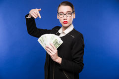 Young girl with a stack of money in the hands of. Young girl with a stack of money in his hands on a blue background stock images
