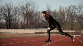 Young girl at the stadium performs muscle stretching exercises. Young and beautiful girl at the stadium in the rays of the setting autumn sun in wireless stock video footage