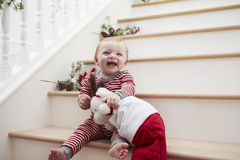 Young Girl On Stairs In Pajamas With Toy At Christmas Stock Photo