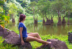 Young girl stand at lake. Woman watching woods outdoor. Stock Photo