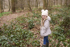 Young girl standing alone in forest undergrowth Stock Images