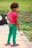 Young girl standing on the bank of Yamuna river in oversized fli. P-flops, Agra, Uttar Pradesh, India. Agra is one of the most populous cities in Uttar Pradesh Royalty Free Stock Photo