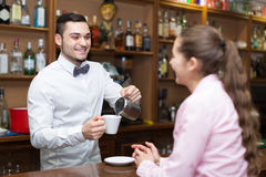 Young girl standing at bar. Happy smiling girl standing at bar and flirting with barman. Focus on guy Royalty Free Stock Photography