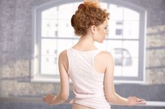 Young girl standing by bar showing her back Royalty Free Stock Images