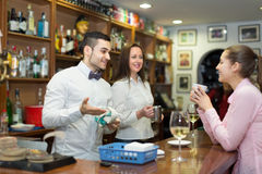 Young girl standing at bar. Smiling young girl standing at bar with cup of coffee. Focus on guy Stock Photo