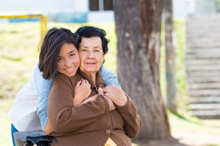 Young girl standing behind grandmother hugging and Royalty Free Stock Photo