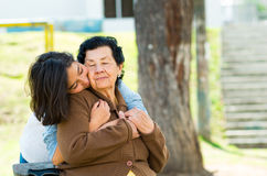 Young girl standing behind grandmother hugging and Stock Image