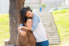Young girl standing behind grandmother hugging and Stock Photo