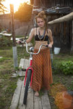 Young girl standing with a Bicycle in the village during sunset. Travel. Stock Photos