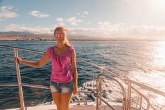 Young girl standing on the boat near the Kauai island stock photos