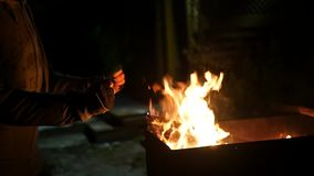 Young girl standing by the campfire at night and warm, rubbing his hands, claps his hands. close-up. 1920x1080 stock video footage