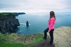 Young girl standing at the cliffs of Moher stock photo
