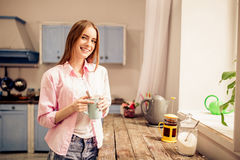 Young girl standing with cup of tea close to window in the kitchen. Female staying at home, looking through window, thinking and enjoying cup of tea Stock Photography