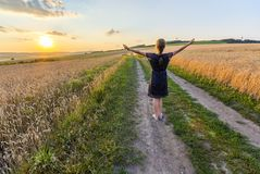 Young girl standing on dirt gravel road in wheat field at sunset. Raising hands royalty free stock photography