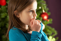 Young Girl Standing In Front Of Christmas Tree Stock Photography