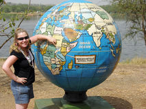 Young girl standing in front of giant world globe. A pretty young lady tourist stands and points to where she is on the map of Africa on this huge globe which stock photos