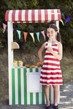 Young girl standing at fruit stand, smiling Stock Photos