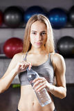 Young girl standing in gym with bottle of water Stock Photo