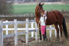 Young girl standing with her horse near paddock royalty free stock photo