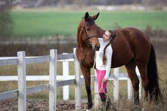 Young girl standing with her horse near paddock stock photo