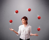 Young girl standing and juggling with red balls Royalty Free Stock Photo