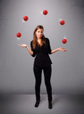 Young girl standing and juggling with red balls. Pretty young girl standing and juggling with red balls Stock Photos