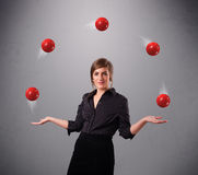 Young girl standing and juggling with red balls. Pretty young girl standing and juggling with red balls Royalty Free Stock Image