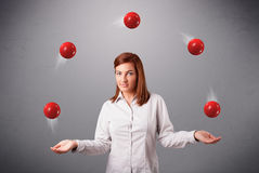 Young girl standing and juggling with red balls. Pretty young girl standing and juggling with red balls Royalty Free Stock Images