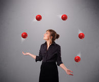 Young girl standing and juggling with red balls Stock Photo