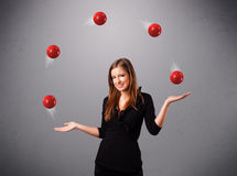 Young girl standing and juggling with red balls. Pretty young girl standing and juggling with red balls Stock Photo