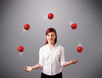 Young girl standing and juggling with red balls Stock Photography
