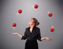 Young girl standing and juggling with red balls. Pretty young girl standing and juggling with red balls Stock Image