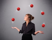Young girl standing and juggling with red balls. Pretty young girl standing and juggling with red balls Stock Photography