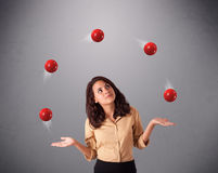 Young girl standing and juggling with red balls Royalty Free Stock Photos