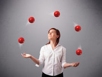 Young girl standing and juggling with red balls. Pretty young girl standing and juggling with red balls Stock Images
