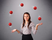 Young girl standing and juggling with red balls Stock Photos