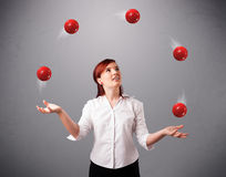 Young girl standing and juggling with red balls. Pretty young girl standing and juggling with red balls Royalty Free Stock Photos