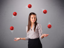 Young girl standing and juggling with red balls Stock Images