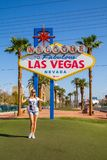 Young girl standing by the Las Vegas sign in Nevada royalty free stock images