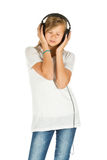 Young girl standing listening to music over white background Stock Photos