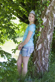 Young girl standing near birch tree Stock Photos