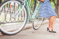 Young girl standing near fence near vintage bike at park Royalty Free Stock Image