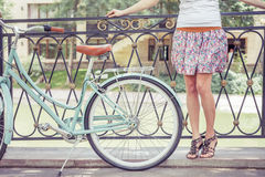 Young girl standing near fence near vintage bike at park Royalty Free Stock Photography