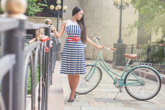Young girl standing near fence near vintage bike at park Stock Image