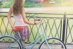 Young girl standing near fence near vintage bike at park Royalty Free Stock Photo
