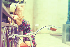 Young girl standing near fence, near vintage city bike Stock Photos