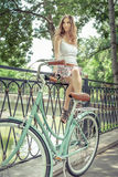 Young girl standing near fence, near vintage city bike Stock Images