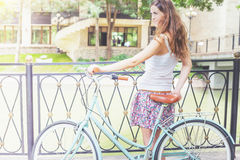 Young girl standing near fence, near vintage city bike Royalty Free Stock Images